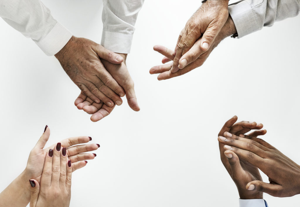 Business people clapping hands together